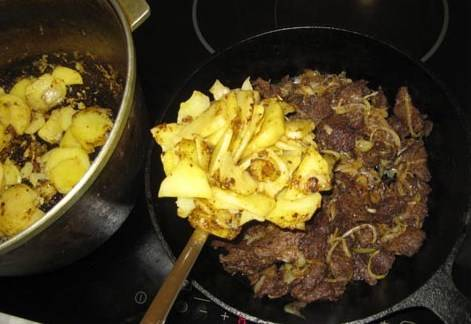 Затем румяный картофель перекладываем к мясу.