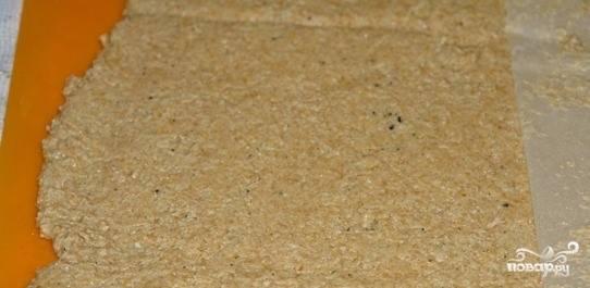 Возьмите силиконовый коврик и выложите на него тесто. При помощи пекарской бумаги раскатайте его в пласт толщиной около трех-четырех миллиметров. Если вы любите хрустящие хлебцы, то раскатайте тесто еще тоньше.