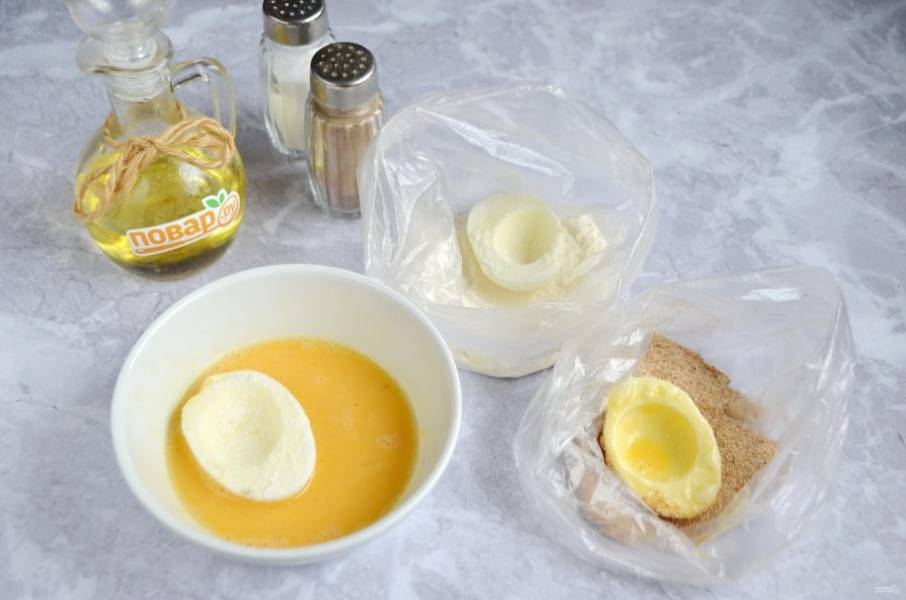 3. Яйца порежьте на половинки, извлеките желтки. Каждую половинку белка запанируйте сначала в муке, потом окуните в яйцо, затем в сухари.