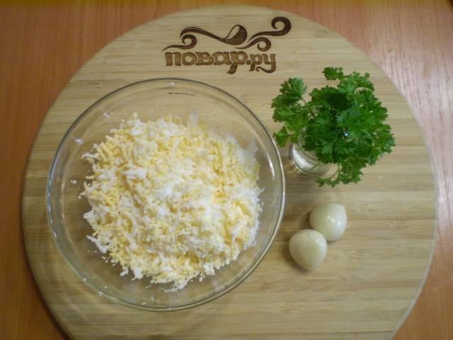 2. Сначала нужно приготовить соус для кабачков. Для это трем вареные яйца, давим чеснок, мелко рубим зелень.