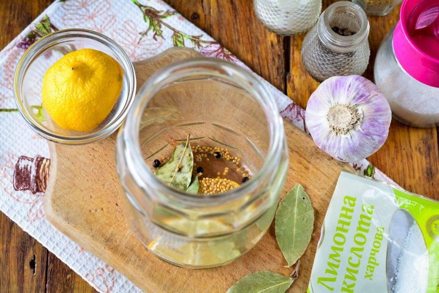 На дно простерилизованной банки выложите специи: лавровый лист, горчицу, перец горошком, чеснок и ломтики лимона.