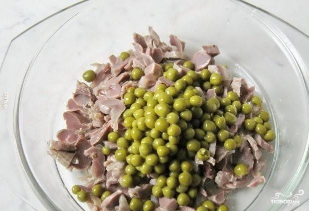 2. Откройте банку с консервированным зеленым горошком. Выложите 100 грамм на сито, чтобы удалить лишний маринад. Затем переложите горошек к желудкам.