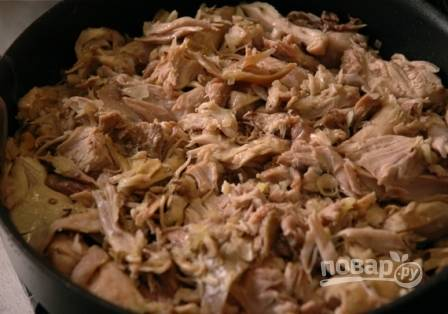 Снимаем мясо с костей и слегка измельчаем его ножом. При желании, чтобы паштет получился более нежным, мясо можно измельчить в блендере. Выкладываем его в глубокую сковороду.