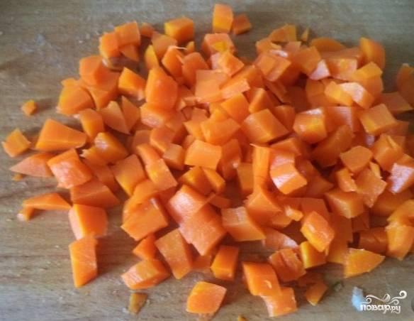 4. Отваренную морковь охладите. Очистите от шкурки и порежьте такими же кусочками, как и картофель.