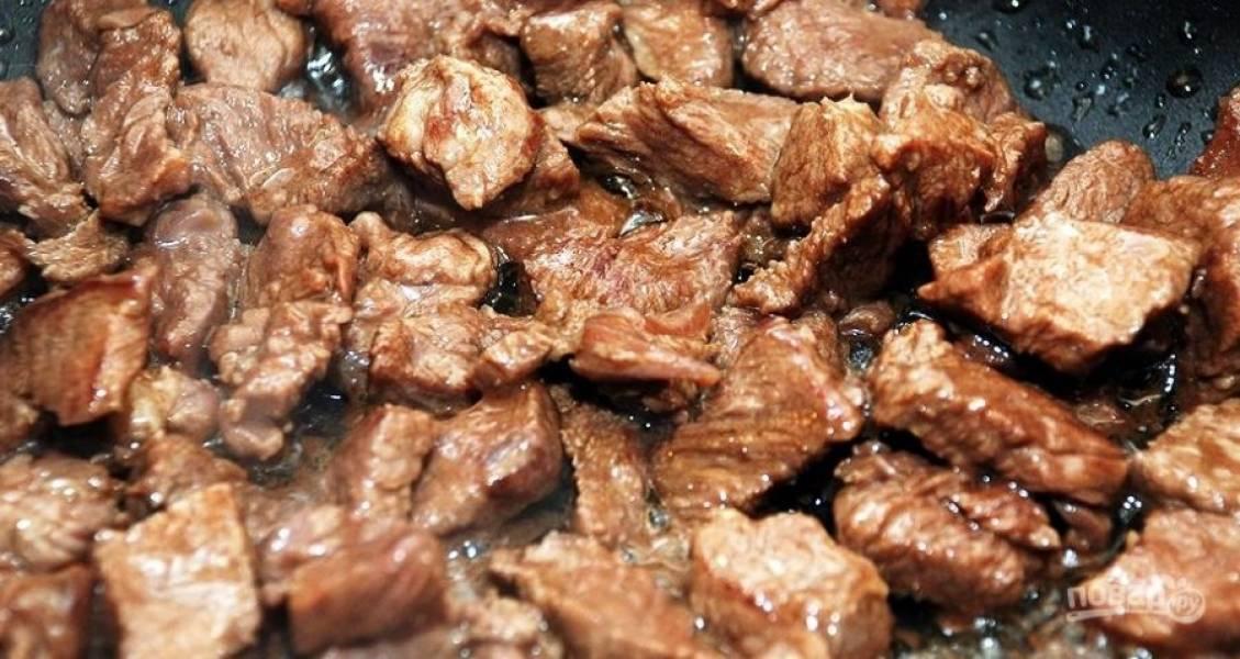 На раскаленную сковороду наливаем небольшое количество растительного масла и начинаем обжаривать предварительно нарезанную на кусочки говядину. Обжариваем до золотистости.