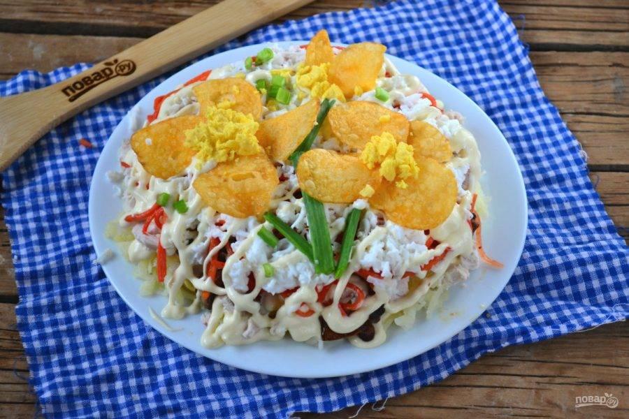 Сверху снова смажьте майонезом. Из картофельных чипсов и измельченного желтка сделайте орхидеи. Украсьте зеленью по вкусу. Салат «Орхидея» готов!