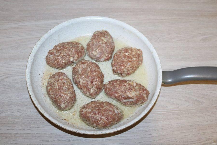 Сформируйте большие котлеты. Обжарьте их на разогретой сковороде в небольшом количестве масла до готовности.