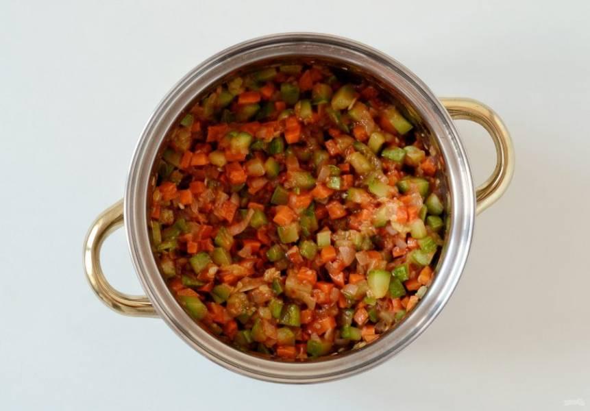 Добавьте к кабачкам лук, морковь, томатную пасту, растительное масло, измельченный чеснок, соль и сахар. Потушите все вместе примерно 20-30 минут. В конце влейте уксус.