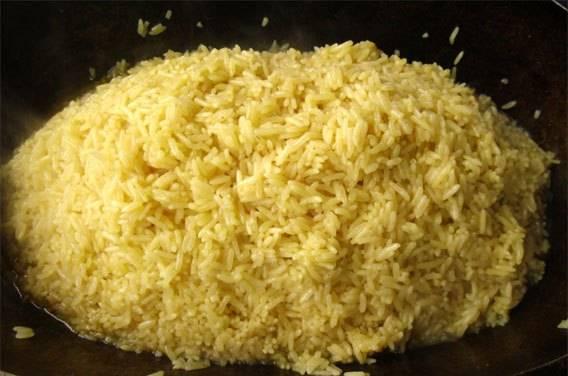 Снова накрываем казан крышкой и оставляем на 15-20 минут. Затем открываем крышку, рис должен впитать всю воду. Насыпаем рис горочкой от краев к центру. Старайтесь в этот момент не подцепить мясо и овощи.