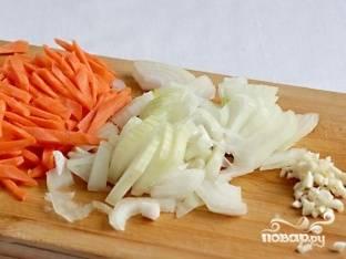 Лук, морковь и чеснок очистите. Морковь помойте и нарежьте соломкой. Лук нарубите четвертинками. Чеснок измельчите.