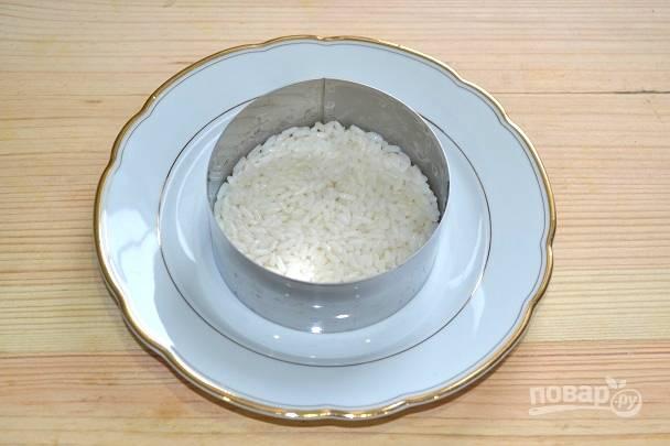 4. Для сборки салата выложите на тарелку сервировочное кольцо. На дно выложите рис, разровняйте.