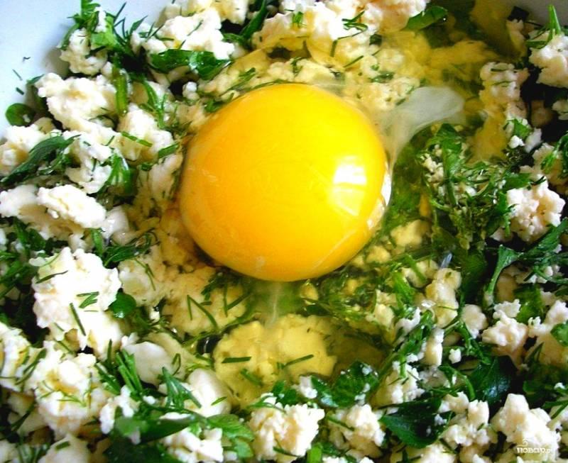 Теперь приступаем к созданию начинки. Вилочкой разминаем брынзу. Нарезаем зелень. Чем больше зелени, тем ярче буде вкус. Трем на терке чеснок или просто мелко рубим его и кладем в начинку. Разбиваем яйца, смешиваем все в однородную кашицу.