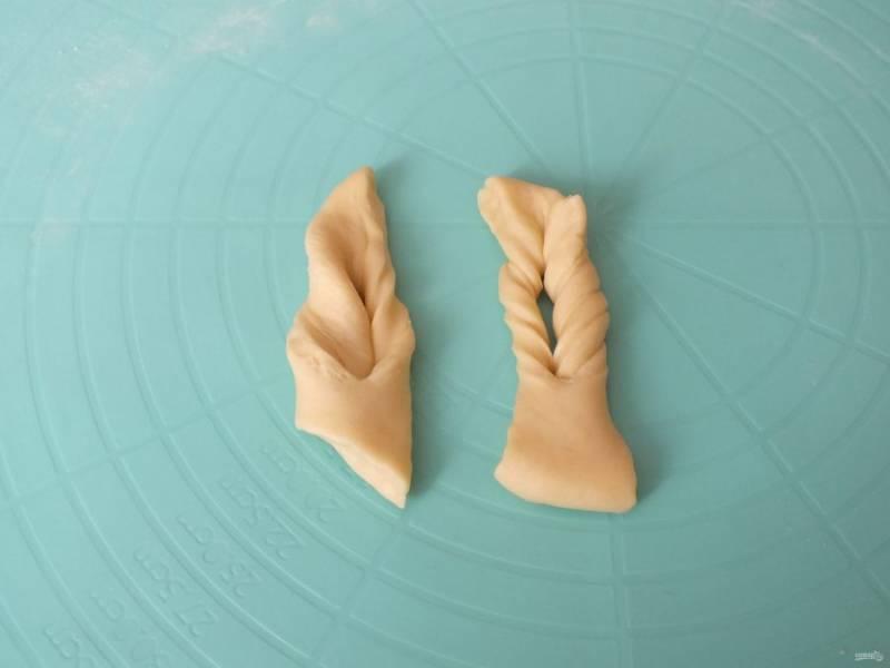 Возьмите один кусочек теста и выверните край в прорезь, подтяните, повторите процесс.