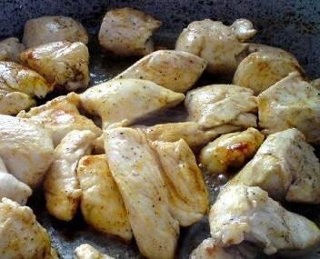 Мясо уже замариновалось, достаём его из тарелки и обсушиваем бумажными салфетками. Сковороду после обжаривания кунжута можно не споласкивать, если семена не пригорели, а сразу смазать оливковым маслом и поставить на огонь для разогревания. В горячую сковороду выкладываем промаринованное мясо курицы и обжариваем его со всех сторон до румяной корочки. На это Вы потратите примерно 4-5 минут. Достаём кусочки шумовкой, сливаем лишнее масло, и выкладываем их на тарелку, где мясо будет остывать перед добавлением в салат. Мясо после обжарки тоже лучше выложить на бумажные полотенца, чтобы они впитали в себя лишний жир, поскольку он нам не нужен ни в салате, не, уж тем более, на наших боках.
