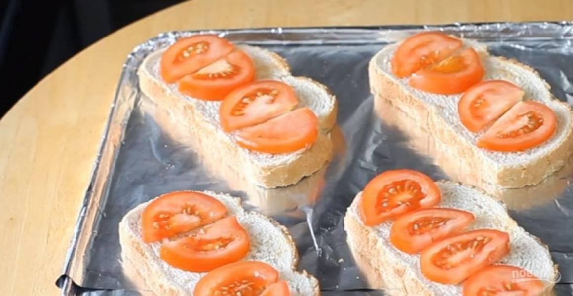 2. Выложите хлеб на покрытый фольгой противень. На батон выложите нарезанные дольками помидоры. Затем выложите нарезанные пластинками сыр и шпроты.
