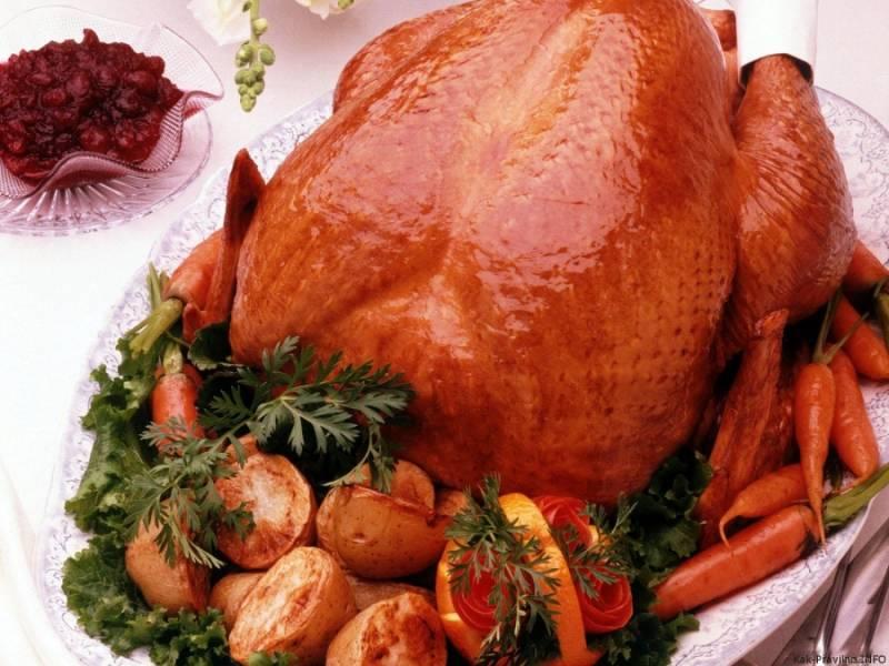 4. Запекается курица в духовом шкафу около 2,5 часов при температуре 180 градусов. Если вы решили запекать ее без рукава, а просто на противне, то каждые полчаса поливайте ее сверху образовавшимся жиром - это даст ей сочность и красивый цвет. После приготовления дайте ей постоять около десяти минут на блюде. Выложить курицу можно на листья салата и вокруг выложить нарезанные овощи. Такой ее и подавать к праздничному или обеденному столу, а разделывается она очень легко (при помощи ножа или кулинарных ножниц).