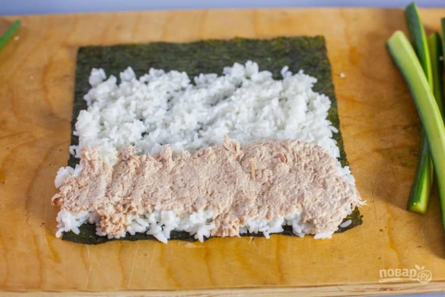 2.Откройте банку тунца, разомните его вилкой, затем разделите содержимое на 4 части, выложите ¼ на половину риса.