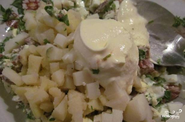 Теперь салат нужно перемешать, посолить и поперчить. Затем добавьте сметану и ещё раз всё перемешайте. Старайтесь перемешивать ингредиенты, чтобы не раздавить картофель и яйца в крошки.