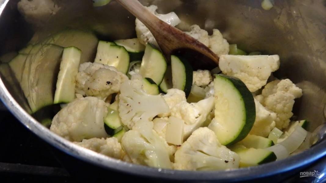 2.В кастрюлю налейте несколько столовых ложек оливкового масла, выложите кабачки, цветную капусту, измельченный чеснок, нарезанную кубиками картошку, оба вида лука. Посолите и поперчите, готовьте, помешивая 5-7 минут.