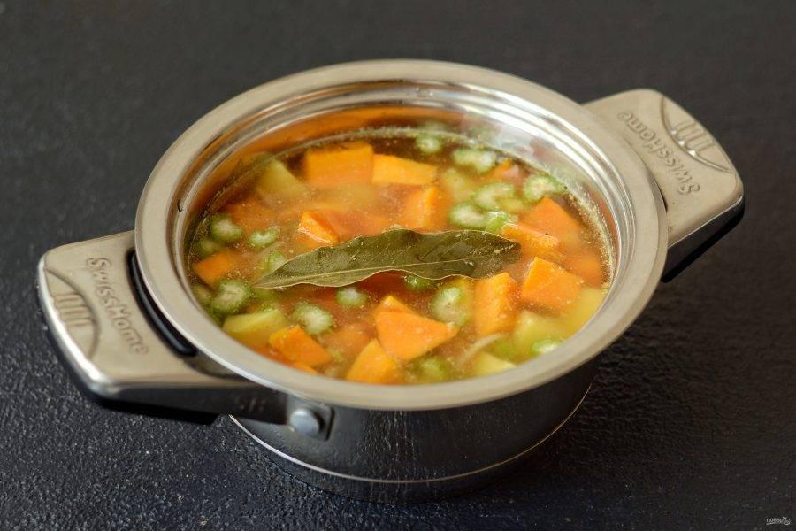 В кастрюлю налейте воду, добавьте бульонный кубик и лавровый лист. Доведите до кипения. Добавьте картошку и тыкву. Варите суп 25 минут на среднем огне.