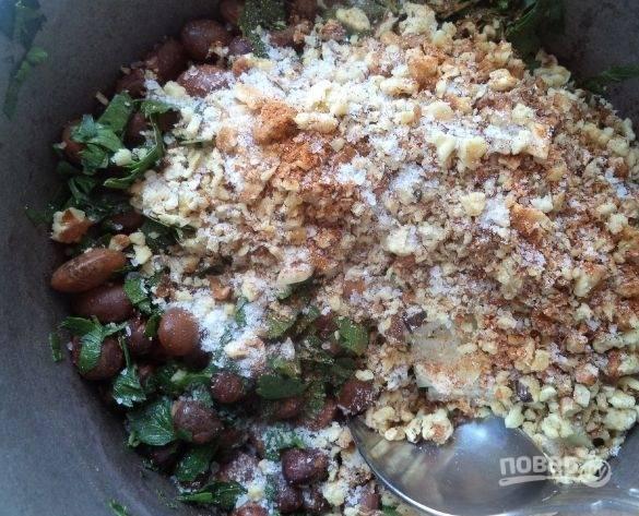 7. Отваренную фасоль выкладываем в казан или вок, добавляем лук, измельченные грецкие орехи. Солим и приправляем по вкусу и обжариваем, постоянно помешивая несколько минут.