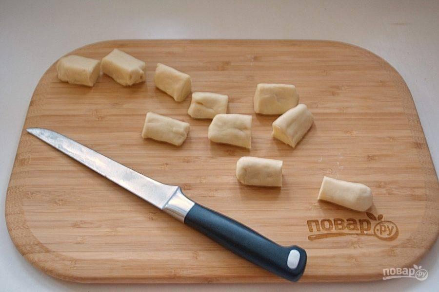Соедините края теста, заключив сыр внутри теста. Колбаску нарежьте на небольшие отрезки.