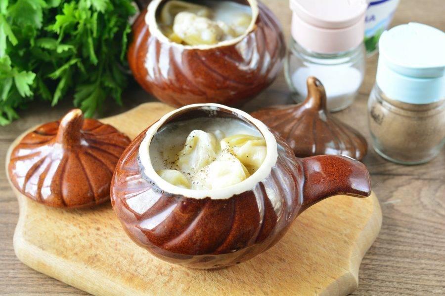 Запекайте пельмени в духовке 20-25 минут при температуре 200 градусов, прикрыв горшочки крышечками.