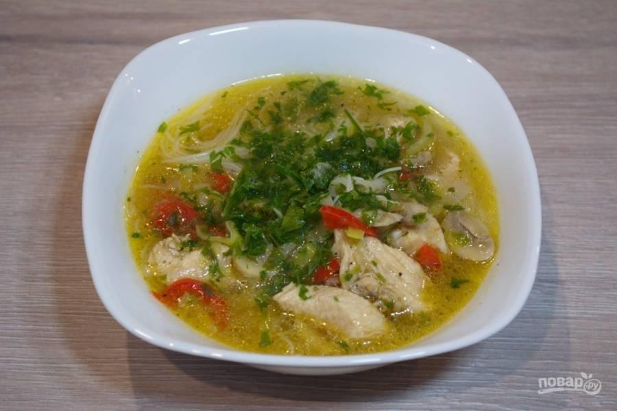 Разлейте суп по мискам, добавив в каждую небольшое количество рисовой лапши. Рисовая лапша длинная. Ее неудобно есть ложкой.  Для удобства лапшу лучше предварительно нарезать на более короткие кусочки. Азиаты едят лапшу палочками, но даже очень хорошие палочки не смогут аккуратно справиться со слишком длинной лапшой. Присыпьте супчик зеленью.