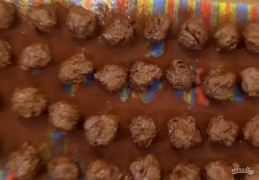 4. Разрежьте на равные части. Наденьте силиконовые перчатки, охладите руки под холодной водой и сформируйте конфеты. Положите их на посыпанную какао доску и отправьте в морозилку на 20 минут.