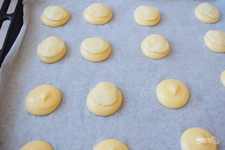 С помощью кондитерского мешка отсадите на противень небольшие порции заварного теста, а сверху выложите небольшие лепешки из кракелинового теста. Поставьте противень в духовку разогретую до 200 градусов на 25-30 минут.
