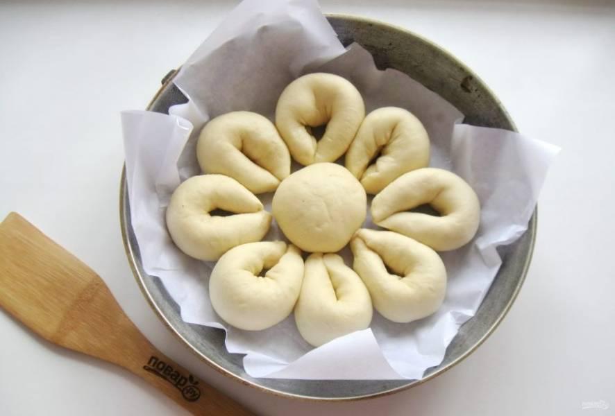 """Выложите заготовки для пирога в форму для выпекания. В середину круглый шарик швом вниз, а по бокам продолговатые """"лепестки""""."""