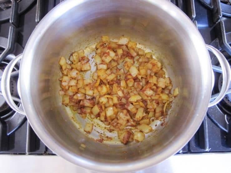 1. В кастрюле с толстым дном разогрейте масло. Обжарьте в нём нарезанный лук в течение 4-х минут. Затем добавьте измельчённый чеснок, соль, тимьян, куркуму, корицу, паприку, кайенский перец и томатную пасту. Готовьте ещё 2 минуты, постоянно помешивая.