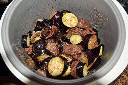 Баклажаны промываем, чтоб смыть соль, затем отжимаем и добавляем к мясу. Готовим 20 минут, крышка открыта.