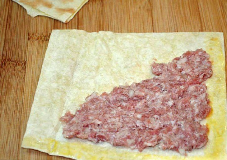 На половину куска лаваша выложите часть фарша, край смажьте яйцом. Заверните вторую половинку лаваша на фарш, прижмите края пальцами. Разогрейте на сковороде растительное масло. Обжарьте самсу из лаваша до золотистой корочки. Дайте лишнему маслу впитаться в бумажную салфетку, затем подавайте блюдо на стол.