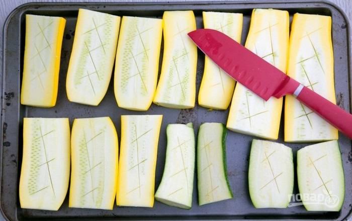3.Вымойте кабачки и разрежьте каждый вдоль, затем каждую половинку разрежьте еще на 2 части. Выложите кабачки на противень. Сделайте неглубокие надрезы.