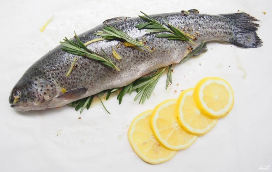 3. Сверху выкладываем розмарин, а внутрь вкладываем лимонные дольки. Также лимонным соком сбрызгиваем рыбу.