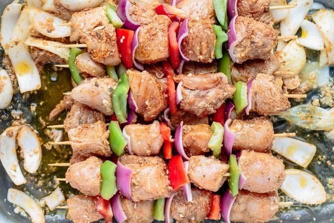 4.Очистите и нарежьте кубиками перцы, красный лук. Распределите мясо и овощи на шампурах.