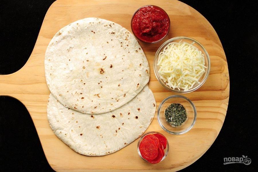 Тортильи выложите на противень. Смажьте их томатным соусом. Сыр крупно натрите.
