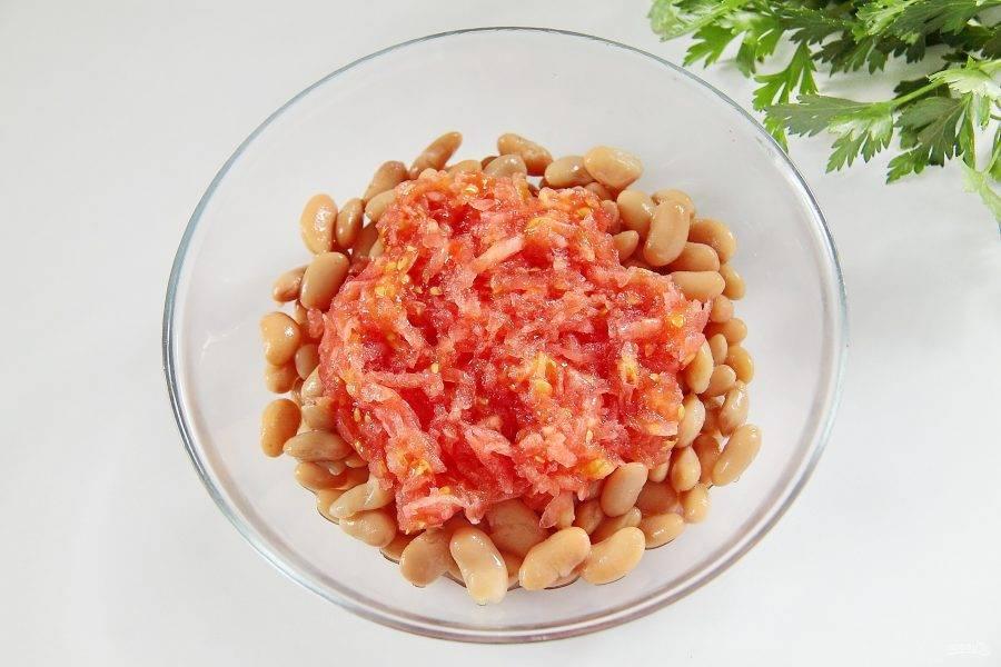 Помидор натрите на терке, шкурку уберите, а мякоть добавьте к фасоли. Если помидор сильно сочный, слейте немного жидкости, чтобы начинка не получилось жидкой.
