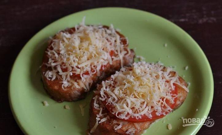 Выложите обжаренные тосты на тарелку. Помидор вымойте и нарежьте кружочками. На хлеб выложите по кружочку помидора. Затем присыпьте все тертым сыром и поставьте в микроволновку, чтобы он расплавился.