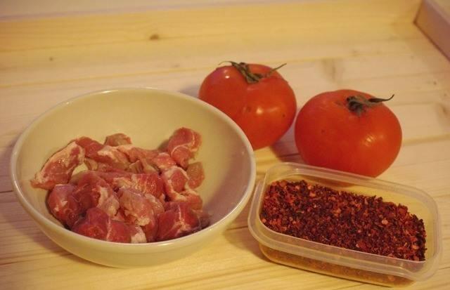 """Порежьте кубиками свинину и помидорки, добавьте их в чашу. Также кладем томатную пасту, щепотку паприки, а сверху заливаем это дело двумя чашками бульона. Переводим мультиварку в режим """"суп""""."""