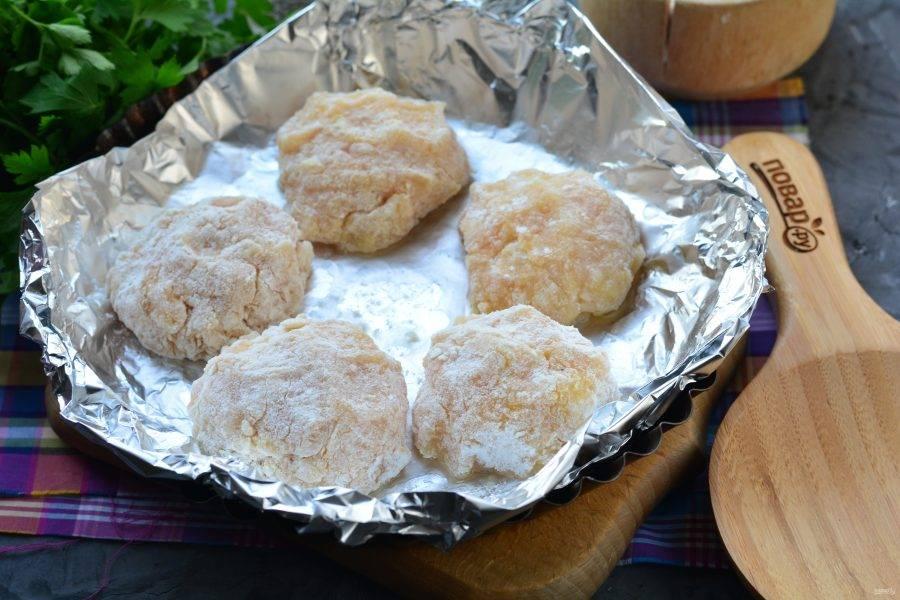 Слепите круглые тефтели, запанируйте в муке и выложите в форму для запекания смазанную маслом.