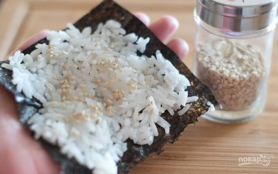 Предварительно отварите рис, очистите креветки, промойте и тонко нарежьте очищенный авокадо. Разрежьте нори на небольшие квадратики. Ложкой равномерно распределите на нем рис и присыпьте по желанию щепоткой кунжута.