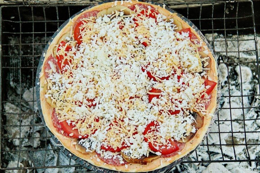 На мангал положите решетку и выложите сверху пиццу. Готовьте над углями, пока нижняя сторона не подрумянится.