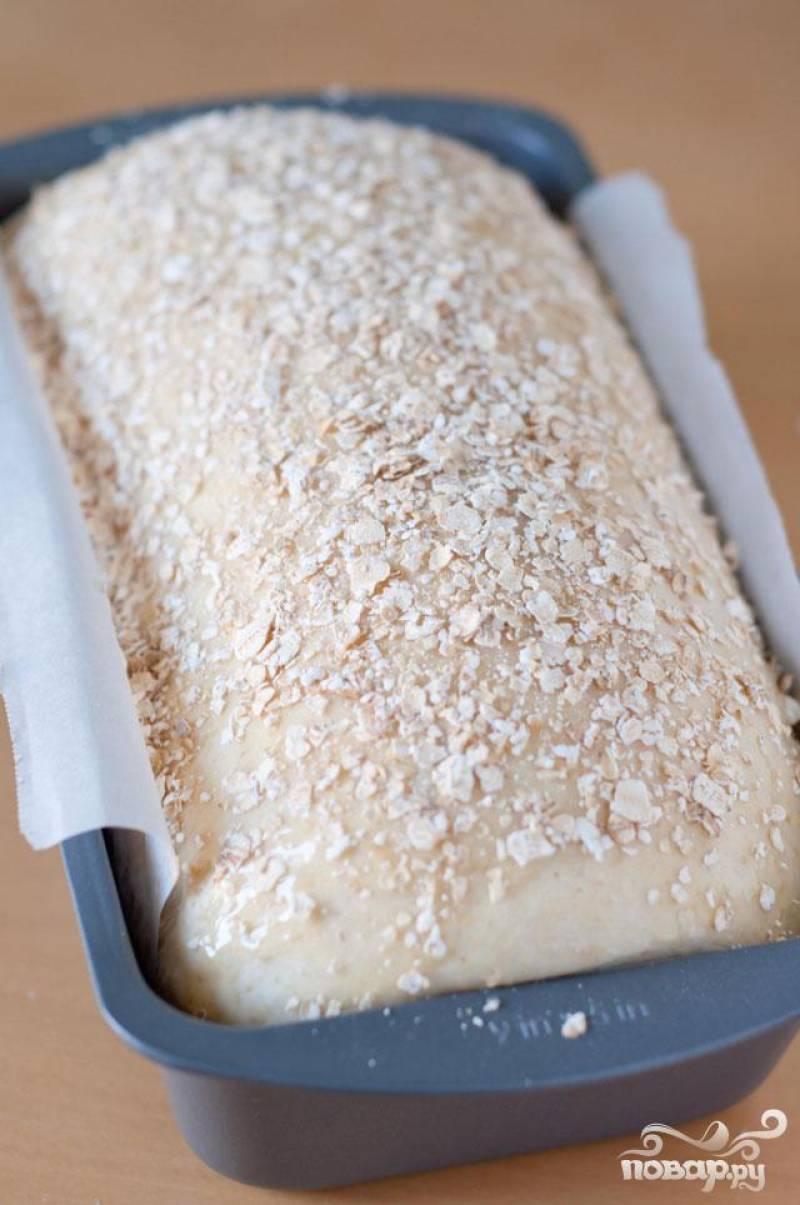 6. Разогреть духовку до 175 градусов. Поместить пустую форму на нижнюю полку духовки и довести в кастрюле 2 чашки воды до кипения. Смазать хлеб разогретым медом и посыпать овсянкой.