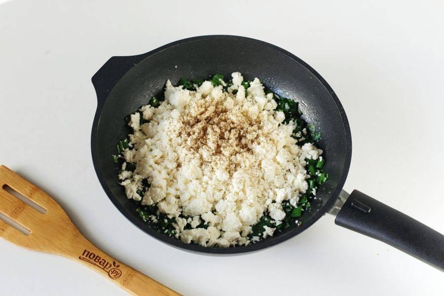 Добавьте к луку тертый сыр (у меня домашний козий сыр, я просто раскрошила его руками), соль если необходимо и молотый перец по вкусу.