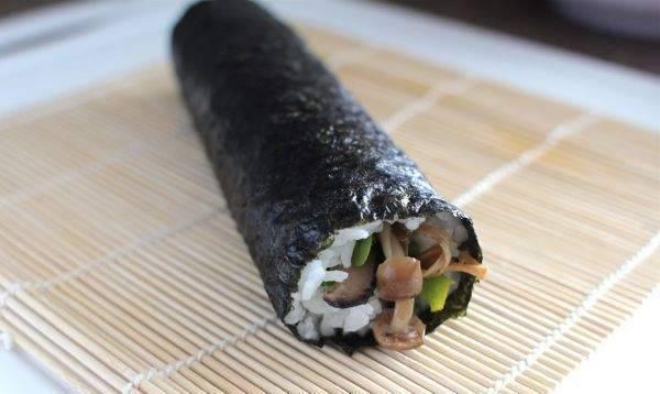 С помощью бамбуковой циновки сверните суши.