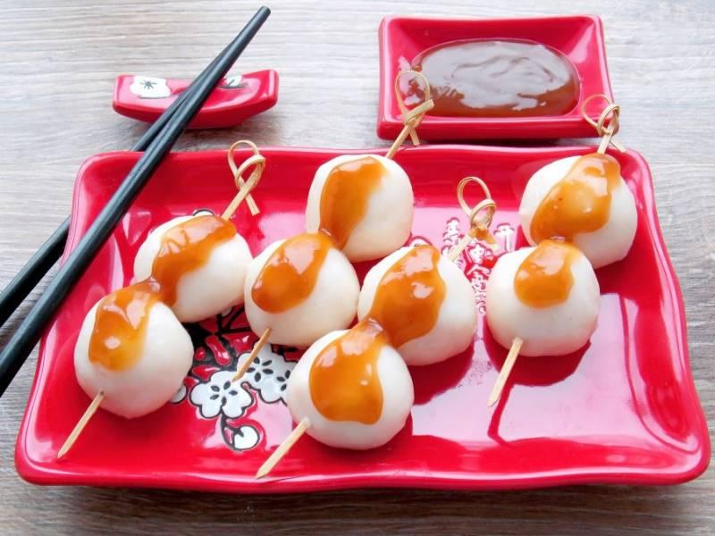 Извлеките решетку с готовыми шариками из пароварки и нанизайте по несколько шариков на деревянные шпажки. Полейте горячий данго приготовленным соусом и сразу подавайте к столу.