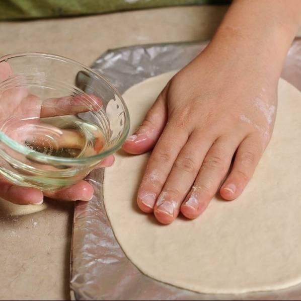 Смажьте поверхность лепешки маслом.