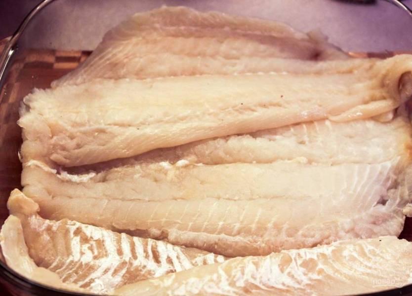 1. Возьмите форму для запекания и смажьте маслом. Вымойте подготовленное филе палтуса и выложите первым слоем.